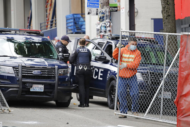 A worker moves new fencing into position on a street outside a Seattle police precinct Monday, June 8, 2020, in Seattle, where protests continued the night before over the death of George Floyd, a black man who was in police custody in Minneapolis. Just days after Seattle's mayor and police chief promised a month-long moratorium on using a type of tear gas to disperse protesters, the department used it again. (AP Photo/Elaine Thompson)