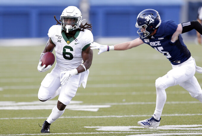 Baylor running back JaMycal Hasty (6) breaks past the tackle attempt by Rice cornerback Andrew Bird (15) during the first half of an NCAA college football game Saturday, Sept. 21, 2019, in Houston. (AP Photo/Michael Wyke)
