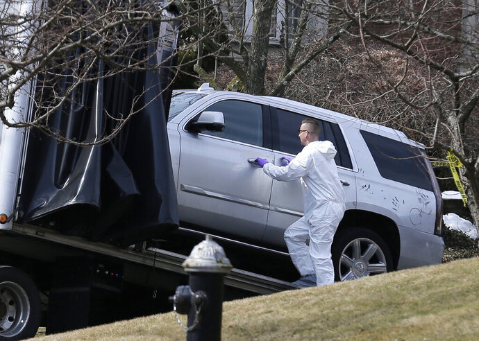Crime scene investigators load a car that appears to have been checked for fingerprints onto a flatbed truck in the Staten Island borough of New York, Thursday, March 14, 2019.  Francesco