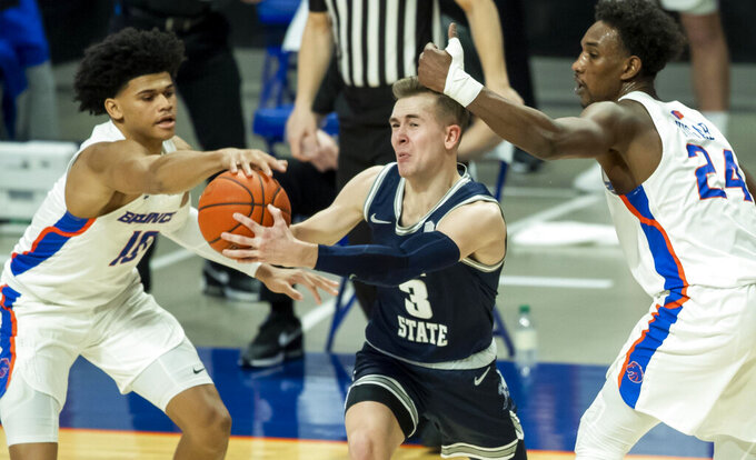 Boise State guard RayJ Dennis, left, steals the ball from Utah State guard Seven Ashworth with defensive help Abu Kigab (24) during an NCAA college basketball game, Wednesday, Feb. 17, 2021 at ExtraMile Arena in Boise, Idaho. (Darin Oswald/Idaho Statesman via AP)