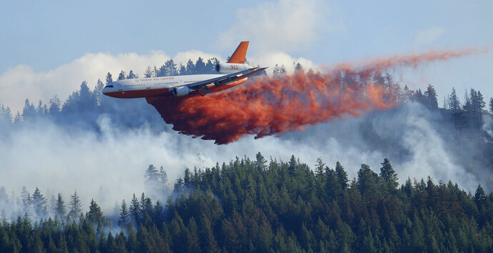 FILE - In this Aug. 21, 2015 file photo, a tanker airplane drops fire retardant on a wildfire burning near Twisp, Wash. The state's commissioner of Public Lands released a proposal Monday, Dec. 2, 2019, that provides some $63 million each year to fight wildfires and take steps to prevent them in the first place. (AP Photo/Ted S. Warren, File)