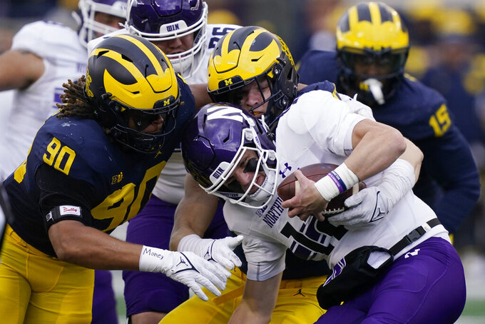 Northwestern quarterback Ryan Hilinski is sacked by Michigan defensive ends Mike Morris (90) and Aidan Hutchinson during the first half of an NCAA college football game, Saturday, Oct. 23, 2021, in Ann Arbor, Mich. (AP Photo/Carlos Osorio)