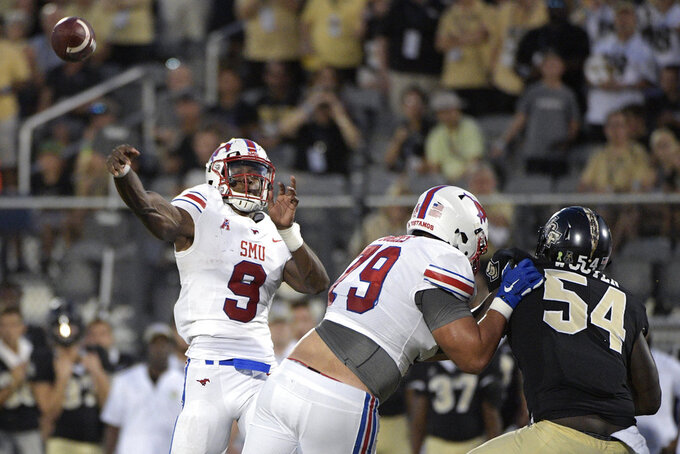 SMU quarterback William Brown (9) throws a pass as offensive lineman Larry Hughes (79) blocks Central Florida defensive lineman A.J. Wooten (54) during the first half of an NCAA college football game Saturday, Oct. 6, 2018, in Orlando, Fla. (AP Photo/Phelan M. Ebenhack)