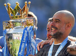 Manchester City coach Pep Guardiola lifts the English Premier League trophy after the English Premier League soccer match between Brighton and Manchester City at the AMEX Stadium in Brighton, England, Sunday, May 12, 2019. Manchester City defeated Brighton 4-1 to win the championship. (AP Photo/Frank Augstein)