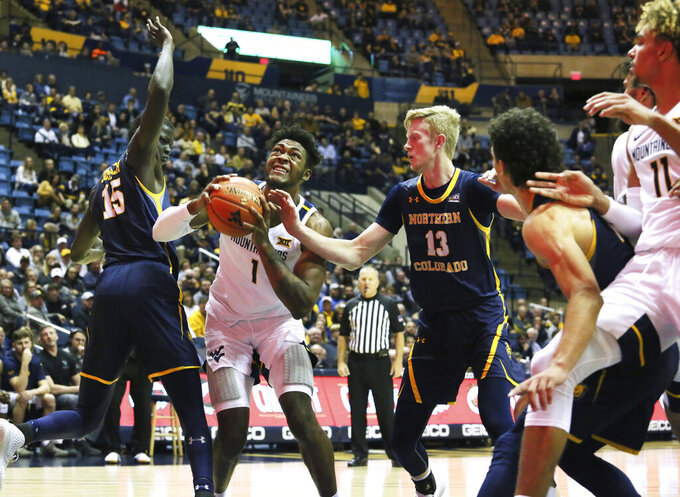West Virginia's Derek Culver(1) is defended by Northern Colorado's Kur Jockuch(15) and Bodie Hume(13) as he goes to make a shot during the first half of an NCAA college basketball game Monday Nov. 18, 2019, Morgantown, W.Va. (AP Photo/Kathleen Batten)
