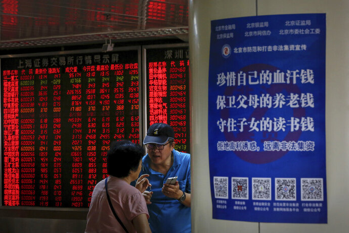 Chinese investors chat each other as they monitor stock prices at the brokerage house in Beijing, Thursday, June 27, 2019. Asian stocks advanced Thursday ahead of a meeting between U.S. President Donald Trump and Chinese leader Xi Jinping at the G-20 summit in Japan this week. (AP Photo/Andy Wong)