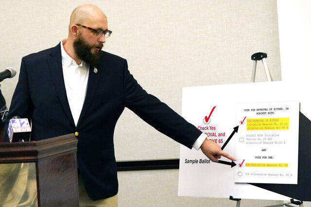 Jonathan C. Brown, 35, a Hattiesburg businessman and former U.S. Air Force staff sergeant, explains how to vote for Initiative 65, a strictly regulated medical marijuana program, that is on the general election ballot this November, during a Wednesday, Oct. 22, 2020 news conference in Jackson, Miss. (AP Photo/Rogelio V. Solis)