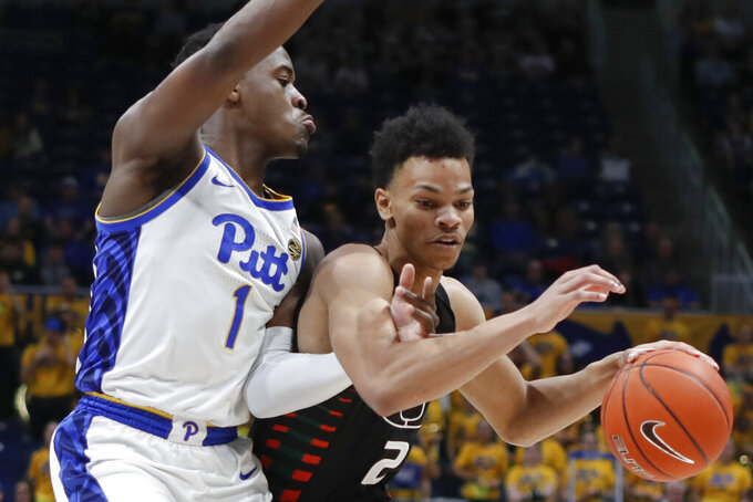Miami's Isaiah Wong (2) drives past Pittsburgh's Xavier Johnson (1) during the first half of an NCAA college basketball game, Sunday, Feb. 2, 2020, in Pittsburgh. (AP Photo/Keith Srakocic)