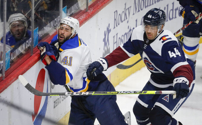 St. Louis Blues defenseman Robert Bortuzzo (41) hits the boards as Colorado Avalanche left wing Kiefer Sherwood (44) chases the puck in the third period of an NHL hockey game in Denver, Friday, April 2, 2021. (AP Photo/Joe Mahoney)