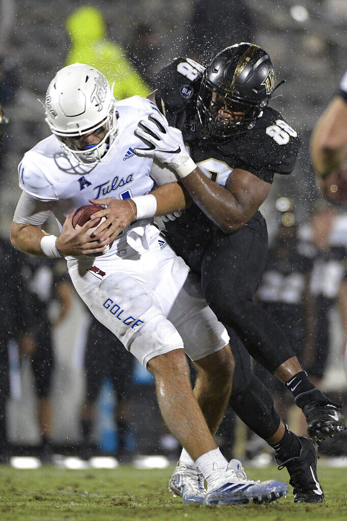 Tulsa quarterback Zach Smith (11) is sacked by Central Florida defensive lineman Joshua Celiscar (88) during the first half of an NCAA college football game Saturday, Oct. 3, 2020, in Orlando, Fla. (AP Photo/Phelan M. Ebenhack)