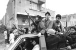 FILE - In this Feb. 12, 1979 file photo, armed rebels, one wearing a gas mask, ride in a truck near the headquarters of Ayatollah Khomeini, in Tehran, Iran. Monday, Feb. 11, 2019 marks the 40th anniversary of the Islamic Revolution. On Feb. 11, 1979, after days of running street battles and uncertainty, Iran's military stood down and allowed the Islamic Revolution to sweep across the country. The caretaker government left behind by the cancer-stricken Shah Mohammad Reza Pahlavi, who weeks earlier left the nation, quickly crumbled as the soldiers once backing it embraced the supporters of Ayatollah Ruhollah Khomeini. (AP Photo/Campion, File)