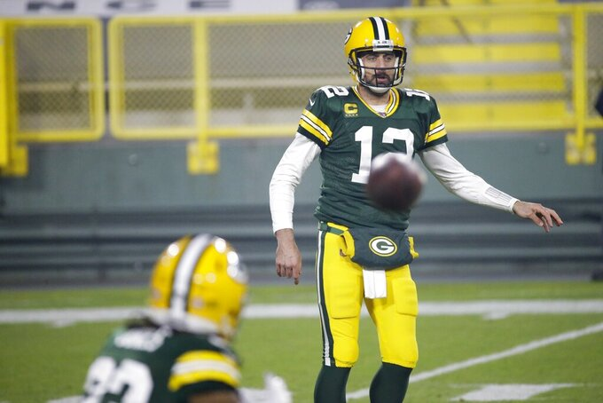 Green Bay Packers' Aaron Rodgers flipos the ball to Aaron Jones during the first half of an NFL football game against the Carolina Panthers Saturday, Dec. 19, 2020, in Green Bay, Wis. (AP Photo/Mike Roemer)