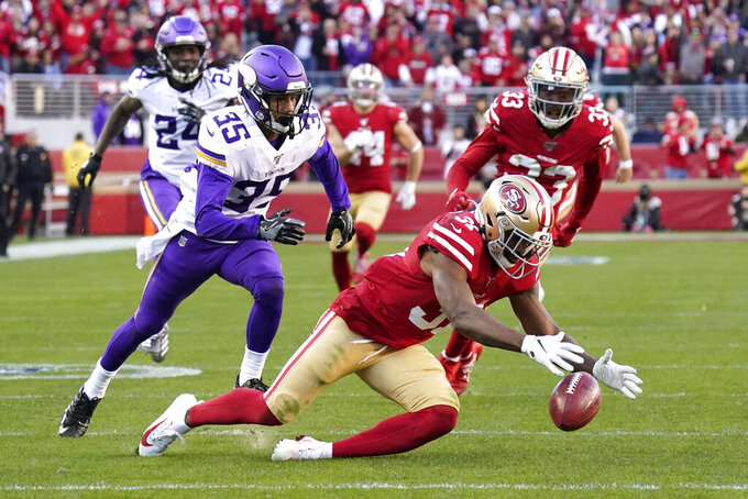San Francisco 49ers' Raheem Mostert, lower right, recovers the ball after Minnesota Vikings' Marcus Sherels (35) couldn't hold on to the ball on a punt return play during the second half of an NFL divisional playoff football game, Saturday, Jan. 11, 2020, in Santa Clara, Calif. (AP Photo/Tony Avelar)