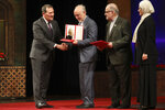 Umran Inan, a Turkish professor of electrical engineering at Stanford University, left, is granted the Mustafa scientific prize by Vice President and head of the Atomic Energy Organization of Iran Ali Akbar Salehi, center, during a ceremony in Tehran, Iran, Monday, Nov. 11, 2019. Iran on Monday awarded a top prize in the study of science and technology to two U.S.-educated scientist, Inan and UCLA professor Ali Khademhosseini, for his work on the application of nanostructures in the treatment of disease. (AP Photo/Vahid Salemi)