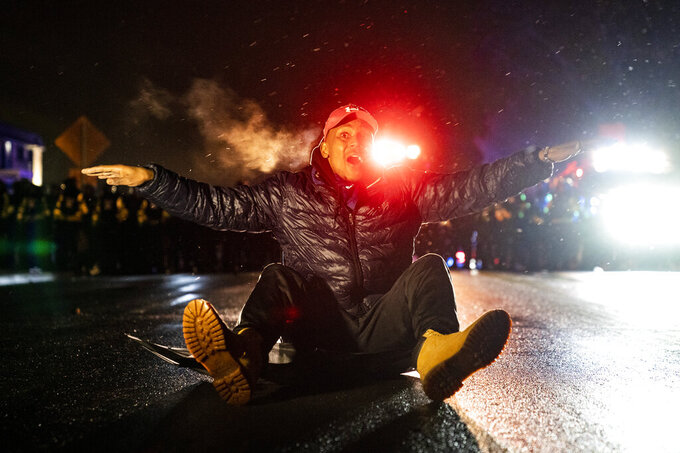 A demonstrator faces off with police outside the Brooklyn Center Police Department while protesting the shooting death of Daunte Wright, late Tuesday, April 13, 2021, in Brooklyn Center, Minn. (AP Photo/John Minchillo)