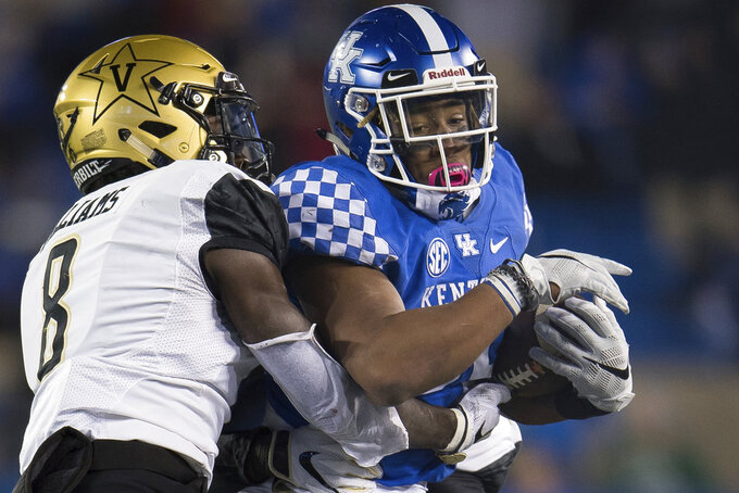 Kentucky running back Benny Snell Jr. (26) is tackled by Vanderbilt cornerback Joejuan Williams (8) during the second half of an NCAA college football game in Lexington, Ky., Saturday, Oct. 20, 2018. Kentucky won, 14-7. (AP Photo/Bryan Woolston)