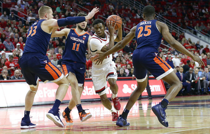 North Carolina State's Markell Johnson drives between Virginia's Jack Salt (33), Ty Jerome (11) and Mamadi Diakite (25) during the first half of an NCAA college basketball game in Raleigh, N.C., Tuesday, Jan. 29, 2019. (AP Photo/Gerry Broome)