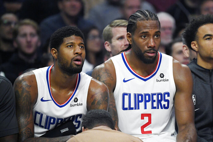 Los Angeles Clippers forward Paul George, left, and forward Kawhi Leonard sit on the bench during the second half of the team's NBA basketball game against the Boston Celtics on Wednesday, Nov. 20, 2019, in Los Angeles. (AP Photo/Mark J. Terrill)