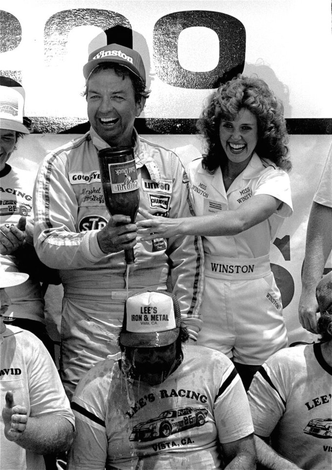 FILE - In this June 5, 1983, file photo, Hershel McGriff empties a bottle of Cold Duck over the head of crew member Snow Thornsberry with the help of Miss Winston, Becky Carter, after winning the Warner Hodgdon 200 NASCAR race at Riverside Raceway in Riverside, Calif. McGriff is a contender for NASCAR's 2021 Hall of Fame class, to be announced Tuesday, June 16, 2020.  (AP Photo/Doug Pizac, File)