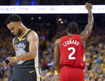Toronto Raptors' Kawhi Leonard raises his fist following a basket as Golden State Warriors' Steph Curry walks away during the second half of Game 6 of basketball's NBA Finals, Thursday, June 13, 2019, in Oakland, Calif. (Frank Gunn/The Canadian Press via AP)