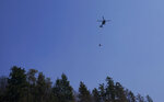 A helicopter flies after making a water drop Wednesday, Sept. 9, 2020, on a wildfire burning in Bonney Lake, Wash., south of Seattle. (AP Photo/Ted S. Warren, Pool)