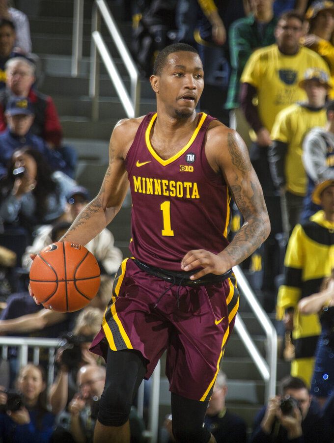 FILE - In this Jan. 22, 2019, file photo, Minnesota guard Dupree McBrayer (1) dribbles the ball in the first half of an NCAA college basketball game against Michigan, in Ann Arbor, Mich. Jordan Murphy has had to slog through a couple of rough seasons at Minnesota to become the Big Ten's second-leading rebounder of all time. Dupree McBrayer is still hurting from his mother's death a little more than three months ago. The seniors still have a chance to end their career with the Gophers on a brighter note. (AP Photo/Tony Ding, File)