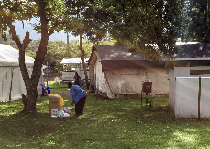 This photo released by the International Rescue Committee (IRC) shows the treatment unit where the confirmed and suspected cases of Ebola are being treated Wednesday, June 12, 2019 at Bwera hospital, Kasese District, in western Uganda near the border with Congo. A 5-year-old boy vomiting blood has become the first cross-border case of Ebola in the current deadly outbreak and now authorities are trying to determine how his family, exposed to the virus, managed to cross from Congo into neighboring Uganda. (Ben Wise/International Rescue Committee via AP)