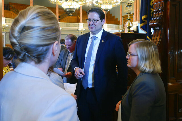 Kansas House Speaker Ron Ryckman Jr., center, R-Olathe, confers with members of his and other Republican leaders' staff as the chamber prepares to adjourn so that lawmakers can start their annual spring break, Thursday, March 19, 2020, at the Statehouse in Topeka, Kan. Lawmakers approved a 10-year, $10 billion transportation program that many of them see as a stimulus to counter the economic damage caused by the coronavirus pandemic. (AP Photo/John Hanna)