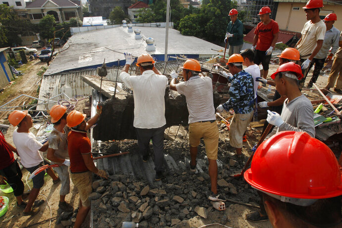 Rescuers try to remove the rubble at the site of a collapsed building in Preah Sihanouk province, Cambodia, Sunday, June 23, 2019. Rescue workers were using saws to cut steel beams and excavators to move piles of rubble of the collapsed seven-story building. (AP Photo/Heng Sinith)
