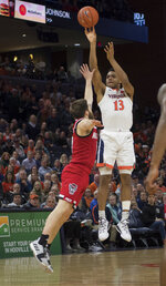 Virginia guard Casey Morsell (13) shoots over North Carolina State guard Braxton Beverly (10) during the second half of an NCAA college basketball game in Charlottesville, Va., Monday, Jan. 20, 2020. (AP Photo/Lee Luther Jr.)