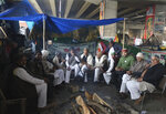Indian Farmers hold a meeting under a flyover as they continue to block a highway leading to Delhi in protest against new farm laws, at Delhi-Uttar Pradesh border, India, Friday, Jan. 22, 2021. Talks between protesting farmers' leaders and the government ended abruptly in a stalemate on Friday with the agriculture minister saying he has nothing more to offer than suspending contentious agricultural laws for 18 months. The farmers' organizations in a statement on Thursday said they can't accept anything except the repeal of the three new laws. (AP Photo/Manish Swarup)