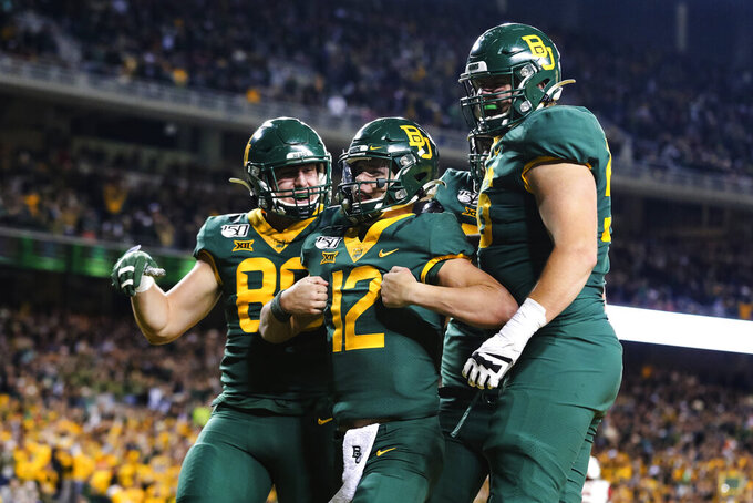 Baylor quarterback Charlie Brewer (12) celebrates his touchdown run with teammates during the first half of an NCAA college football game against Oklahoma in Waco, Texas, Saturday, Nov. 16, 2019. (AP Photo/Ray Carlin)
