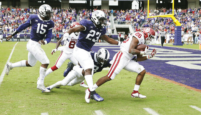 FILE - In this Oct. 20, 2018, file photo, Oklahoma running back Kennedy Brooks (26) battles past TCU defensive end Ben Banogu (15), linebacker Alec Dunham (23) and safety Markell Simmons (3) to score a touchdown during the first half of an NCAA college football game, in Fort Worth, Texas. Oklahoma won 52-27. Oklahoma might have found its newest freshman phenom at running back in Kennedy Brooks. He ran for 168 yards against TCU (AP Photo/Brandon Wade)