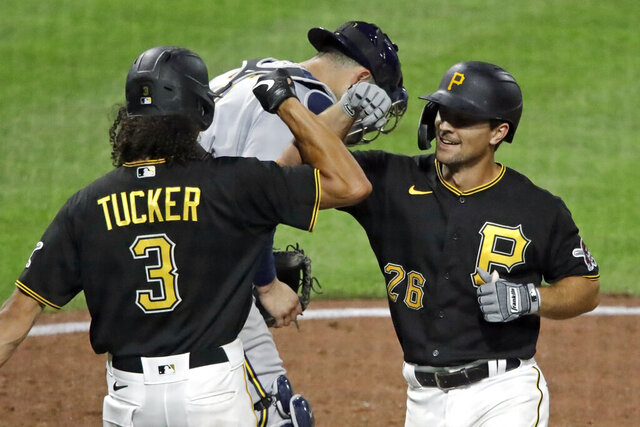 Pittsburgh Pirates' Adam Frazier (26) celebrates with Cole Tucker (3) as he crosses home plate in front of Milwaukee Brewers catcher Manny Pina after hitting a two-run home run off relief pitcher Bobby Wahl during the eighth inning of an baseball game in Pittsburgh, Tuesday, July 28, 2020. (AP Photo/Gene J. Puskar)