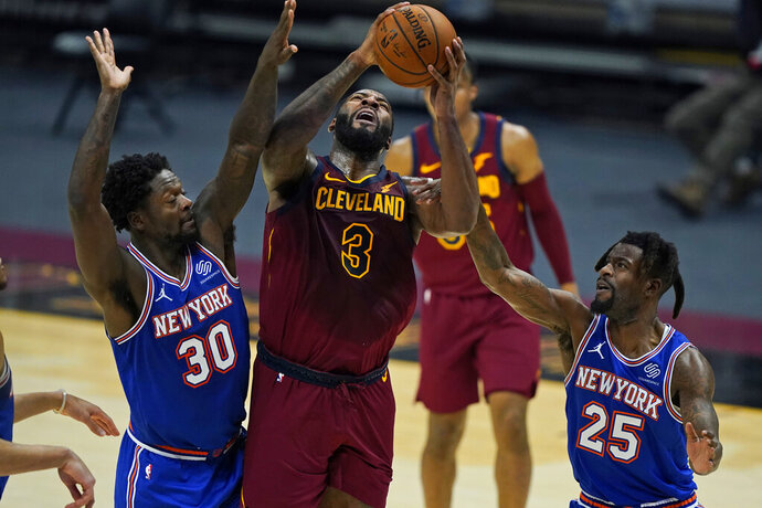 Cleveland Cavaliers' Andre Drummond (3) drives to the basket against New York Knicks' Julius Randle (30) and Reggie Bullock (25) during the first half of an NBA basketball game Friday, Jan. 15, 2021, in Cleveland. (AP Photo/Tony Dejak)