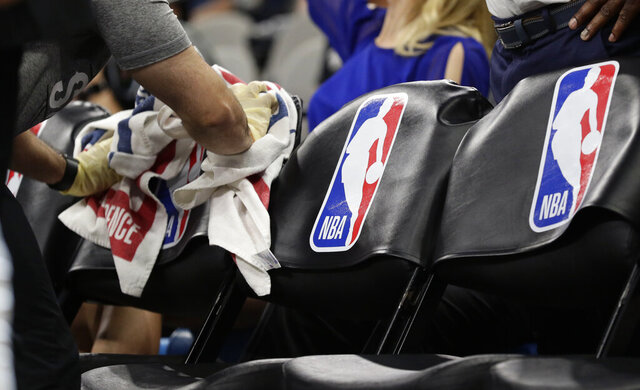 A team attendant uses protective gloves to wipe down seats in the players' bench area during an NBA basketball game between the San Antonio Spurs and the Dallas Mavericks in San Antonio, Tuesday, March 10, 2020. (AP Photo/Eric Gay)