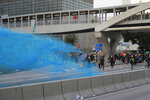 A police vehicle sprays blue-colored water towards anti-government protesters during a demonstration near Central Government Complex in Hong Kong, Sunday, Sept. 15, 2019. Police fired a water cannon and tear gas at protesters who lobbed Molotov cocktails outside the Hong Kong government office complex Sunday, as violence flared anew after thousands of pro-democracy supporters marched through downtown in defiance of a police ban. (AP Photo/Kin Cheung)