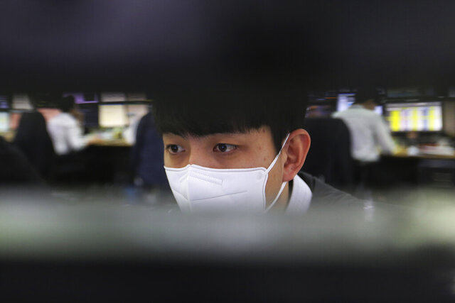A currency trader watches monitors at the foreign exchange dealing room of the KEB Hana Bank headquarters in Seoul, South Korea, Thursday, Feb. 6, 2020. Asian stock markets have surged after President Donald Trump was acquitted in an impeachment trial and China promised tax cuts and other help to businesses reeling from a virus outbreak. (AP Photo/Ahn Young-joon)