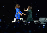 Michelle Obama, left, and Oprah Winfrey greet each other onstage at