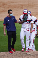 Chicago White Sox relief pitcher Gio Gonzalez, right, is checked by a team trainer after an injury during the seventh inning of a baseball game against the Chicago Cubs in Chicago, Sunday, Sept. 27, 2020. (AP Photo/Nam Y. Huh)
