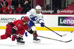Carolina Hurricanes defenseman Brett Pesce (22) reaches as Tampa Bay Lightning center Blake Coleman (20) shoots during the first period of an NHL hockey game in Raleigh, N.C., Monday, Feb. 22, 2021. (AP Photo/Gerry Broome)
