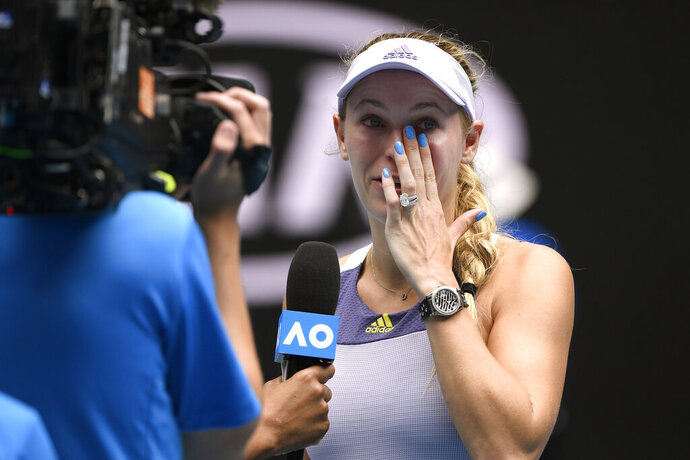 Denmark's Caroline Wozniacki wipes away tears after a third round loss to Tunisia's Ons Jabeur at the Australian Open tennis championship in Melbourne, Australia, Friday, Jan. 24, 2020. (AP Photo/Andy Brownbill)