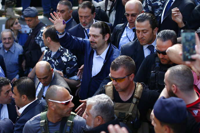 FILE - In this Sunday, May 8, 2016 file photo, Former Lebanese Prime Minister Saad Hariri, center, leader of Lebanon's parliamentary majority, waves to his supporters after he voted at a polling station during the municipal elections in Beirut, Lebanon. An explosion occurred earlier in June 2020 near the convoy of former Lebanese Prime Minister Saad Hariri when he was on a visit in a mountainous region in Lebanon's eastern Bekaa Valley, a Saudi-owned TV station reported Sunday, June 28. (AP Photo/Hassan Ammar, File)