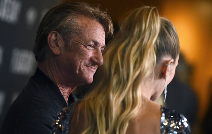 """Cast member Sean Penn, left, looks at his daughter, Dylan Penn, who plays his daughter in the movie as well, during an interview at the Los Angeles premiere of """"Flag Day"""" at the Directors Guild of America Theater on Wednesday, Aug. 11, 2021, in Los Angeles. (Photo by Jordan Strauss/Invision/AP)"""