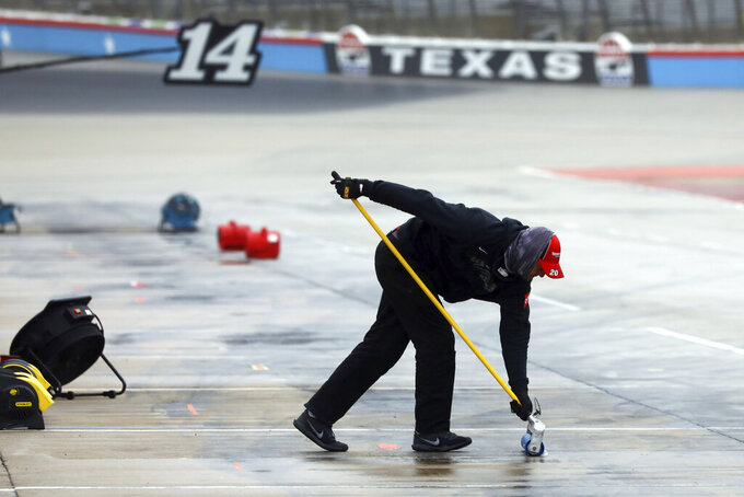 A member of Erik Jones pit crew squeegees water out of the pit area as crews prepare to resume a NASCAR Cup Series auto race at Texas Motor Speedway in Fort Worth, Texas, Tuesday, Oct. 27, 2020. The race was stopped on Sunday because of drizzle and misty conditions that allowed drivers to complete just 52 of 334 laps. Another 115 laps have to be completed to get to the halfway mark of 167 laps that would make Texas an official race.. (AP Photo/Richard W. Rodriguez)