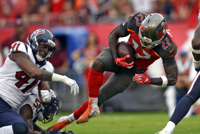 Tampa Bay Buccaneers running back Ronald Jones II (27) gets by Houston Texans inside linebacker Zach Cunningham (41) on a 4-yard score during the first half of an NFL football game Saturday, Dec. 21, 2019, in Tampa, Fla. (AP Photo/Jason Behnken)