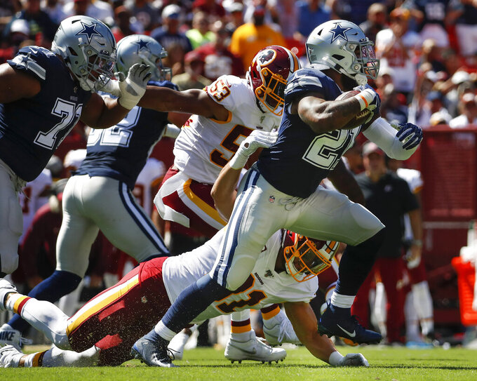 Dallas Cowboys running back Ezekiel Elliott (21) breaks away from Washington Redskins outside linebacker Ryan Kerrigan (91) in the first half of an NFL football game, Sunday, Sept. 15, 2019, in Landover, Md. (AP Photo/Alex Brandon)
