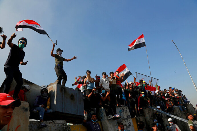 Protesters celebrate while taking control of some concrete walls and barriers set by security forces to close Sinak bridge leading to the Green Zone government areas during clashes between Iraqi security forces and anti-government demonstrators in Baghdad, Iraq, Saturday, Nov. 16, 2019.  Iraqi security and medical officials say protesters have pushed closer to the Green Zone, Baghdad's fortified seat of government, after security forces pulled back following a night of violent altercations.(AP Photo/Khalid Mohammed)