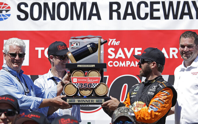 Martin Truex Jr., third from left, celebrates after winning a NASCAR Sprint Cup Series auto race Sunday, June 23, 2019, in Sonoma, Calif. (AP Photo/Ben Margot)