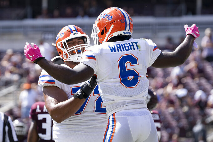 Florida running back Nay'Quan Wright (6) celebrates with teammate Stone Forsythe (72) after a short touchdown run against Texas A&M during the second quarter of an NCAA college football game, Saturday, Oct. 10, 2020, in College Station, Texas. (AP Photo/Sam Craft)